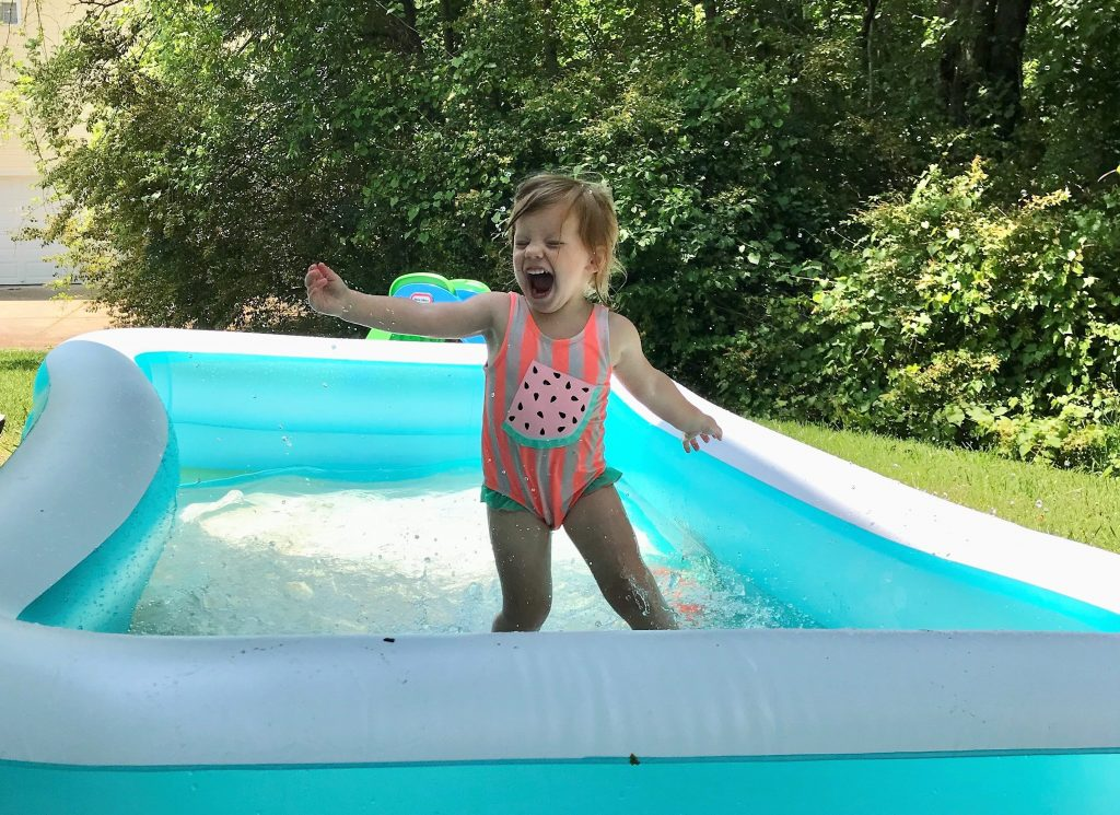 Little girl excited about the beauty of playing in a pool outside